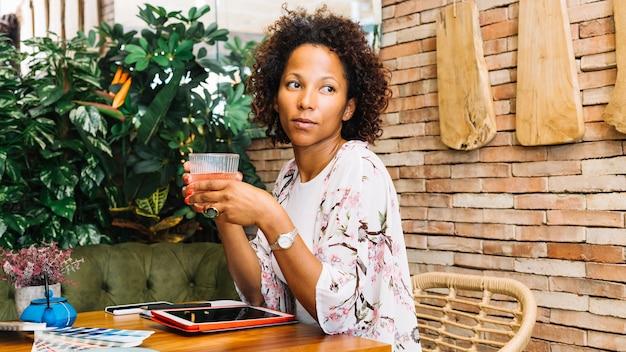 Een afrikaanse jonge vrouw het drinken cocktail in het restaurant Gratis Foto