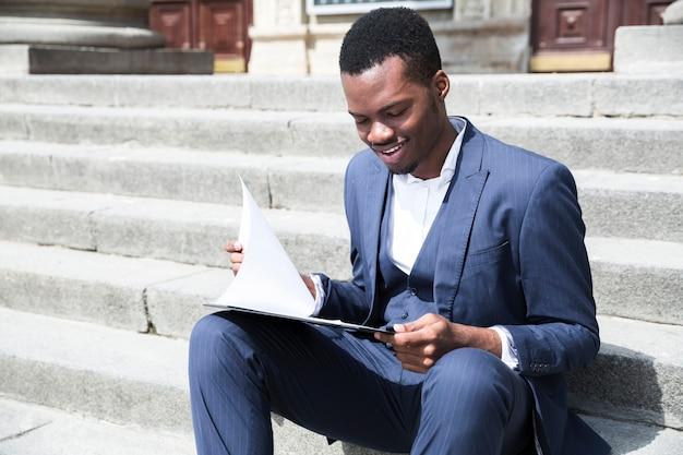 Een afrikaanse jonge zakenman die op mobiele telefoonzitting op trap met laptop spreekt Gratis Foto