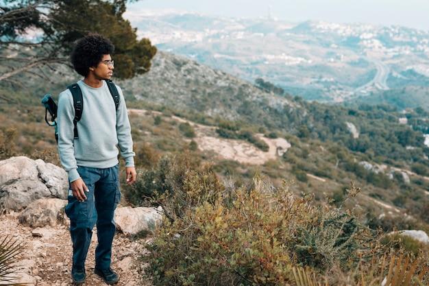 Een afrikaanse jongeman met uitzicht op de berg Gratis Foto