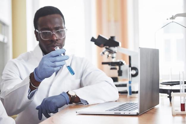 Een afro-amerikaanse werknemer werkt in een laboratorium en voert experimenten uit. Gratis Foto