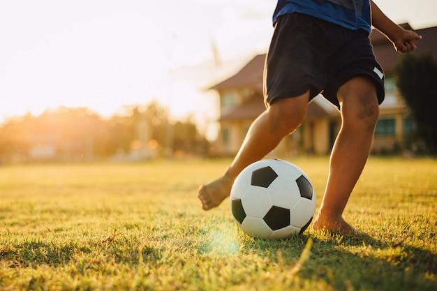 Een agroup van kinderen voetballen voor oefening in landelijk plattelandsgebied onder de zonsondergang Premium Foto