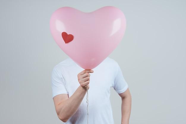 Een anonieme man in een wit t-shirt met een hartvormige ballon. fijne valentijnsdag. Premium Foto