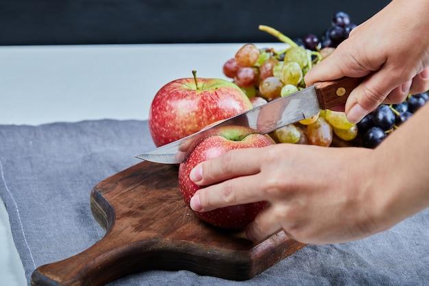 Een appel snijden op het fruitbord met druiven eromheen. Gratis Foto
