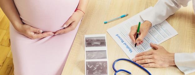 Een arts in een kliniek onderzoekt een zwangere vrouw. Premium Foto