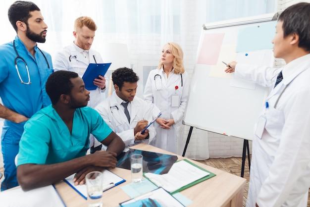 Een arts toont papier van andere artsen op een wit bord. Premium Foto