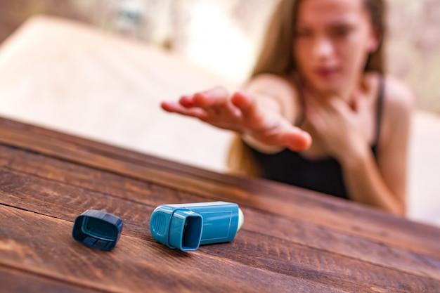 Een astmatisch persoon probeert de inhalator te bereiken tijdens een astma-aanval Premium Foto