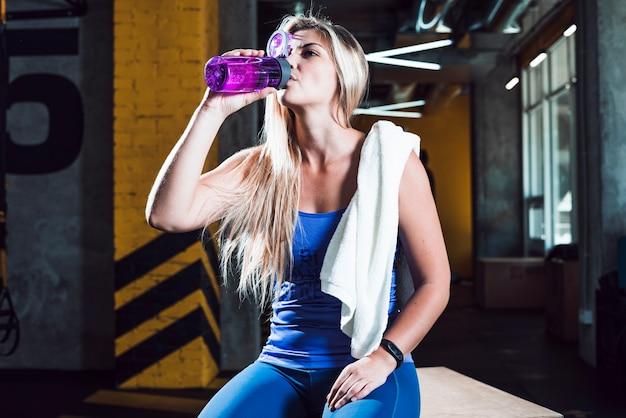 Een atletisch vrouwen drinkwater in gymnastiek Gratis Foto