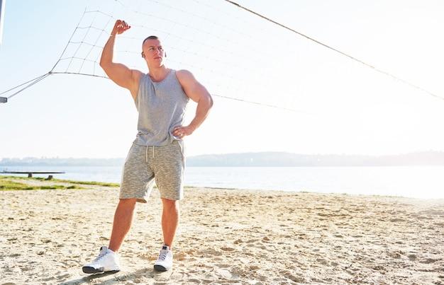 Een atletische man kijkt naar zee op wild zandstrand. Gratis Foto