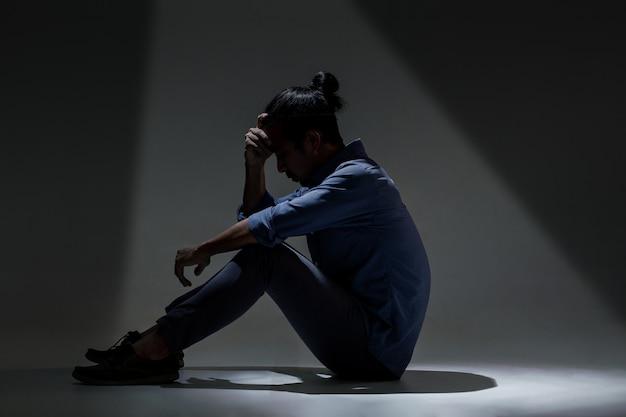 Een aziatische man lijdt aan depressies in de duisternis. Premium Foto