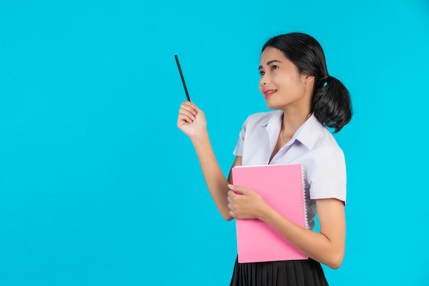 Een aziatische studente met een met haar roze notitieboekje op een blauw. Gratis Foto