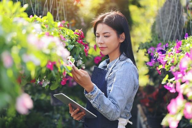 Een aziatische vrouw die eigenaar is van een bloementuinbedrijf, telt de bloemen in overeenstemming met de bestelling van de klant. Premium Foto