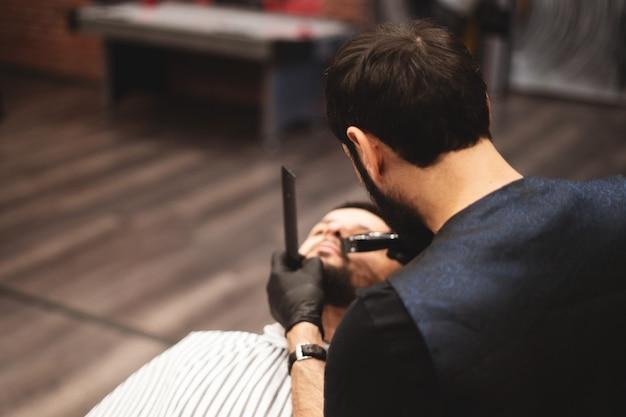 Een baard scheren in een kapperszaak met een gevaarlijk scheermes. kapper winkel baardverzorging. drogen, knippen, een baard knippen. selectieve aandacht. Premium Foto