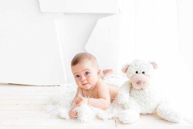 Een baby met een teddybeer ligt in een lichte kamer Premium Foto