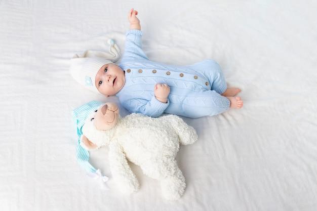 Een baby op een bed in een kap gaat naar bed of wordt 's ochtends wakker. textiel en beddengoed voor kinderen. pasgeboren baby met een stuk speelgoed beer Premium Foto