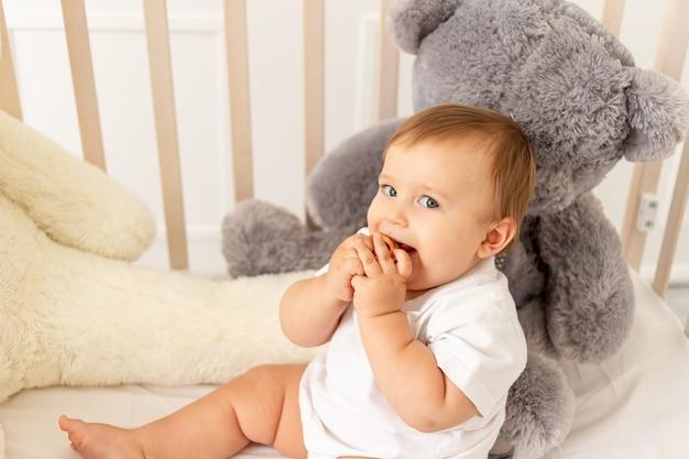 Een babyjongen van zes maanden oud zit in zijn wieg met grote teddyberen in een lichte kamer Premium Foto