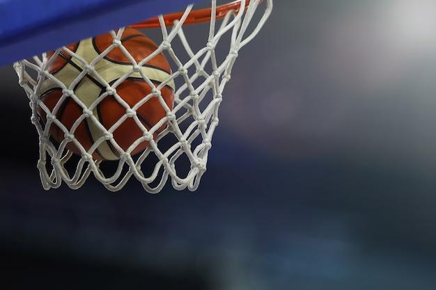 Een basketbal vliegt de ring in. sportcomplex Premium Foto