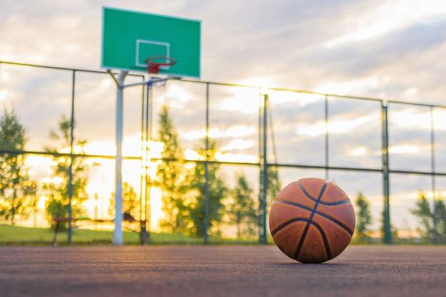 Een basketbalbal ligt op de grond op de achtergrond van een schild en een avondhemel Premium Foto