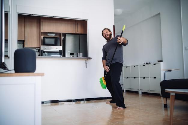 Een bebaarde man die een pyjama draagt, gebruikt een sweep om een gitaar te simuleren terwijl hij de vloer van zijn woonkamer bezems terwijl hij naar muziek luistert uit slimme luidsprekers Premium Foto