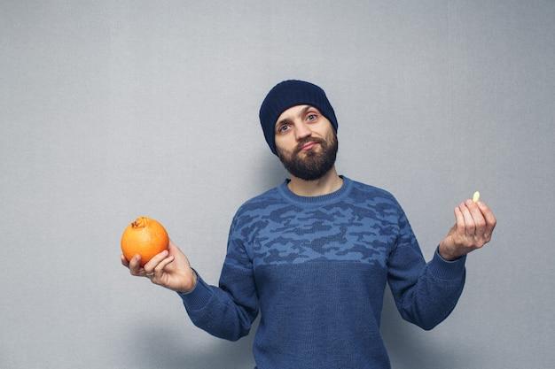 Een bebaarde man heeft een sinaasappel en een zetpil voor aambeien in zijn handen. aambeien concept. Premium Foto