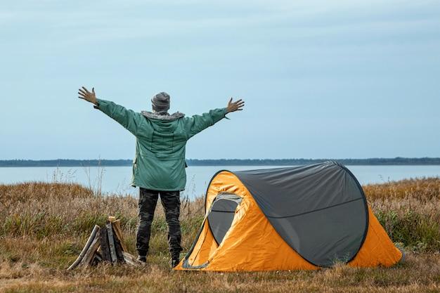 Een bebaarde man in de buurt van een camping tent in oranje natuur en het meer. reizen, toerisme, kamperen. Premium Foto