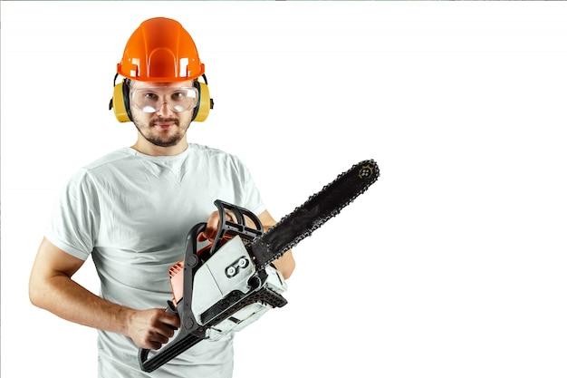 Een bebaarde man in een helm met een kettingzaag op een witte achtergrond. Premium Foto