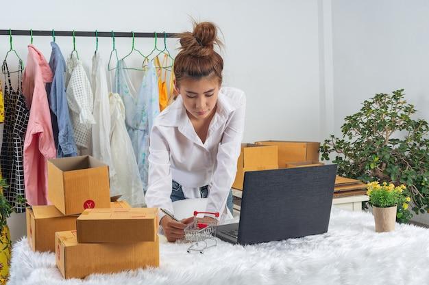 Een bedrijfsvrouw werkt online en traint om de verpakking van het klanten thuis bureau op muur te antwoorden. Gratis Foto