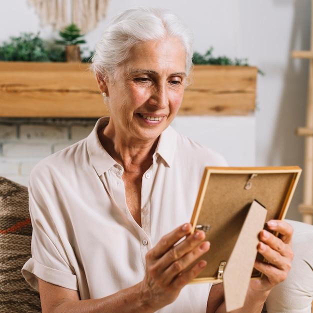 Een bejaarde die fotoframe bekijkt Gratis Foto
