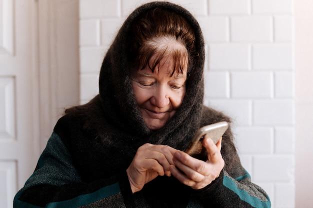 Een bejaarde grootmoeder heeft voor het eerst een mobiele telefoon Premium Foto