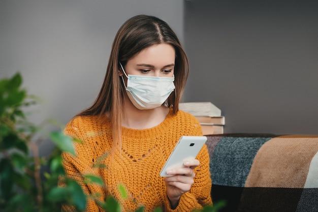 Een bezorgd meisje zit thuis in quarantaine-isolatie, heeft een mobiele telefoon en leest nieuws over het coronovirus. Premium Foto