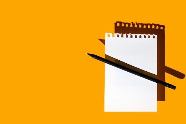 Een blanco vel kladblok, zwart potlood en harde schaduwen op fel geel Premium Foto