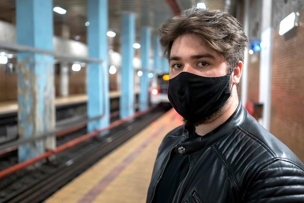 Een blanke man met baard in zwart medisch masker op zoek naar de camera in de metro Gratis Foto
