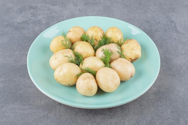 Een blauw bord van gekookte aardappelen met verse dille. Gratis Foto
