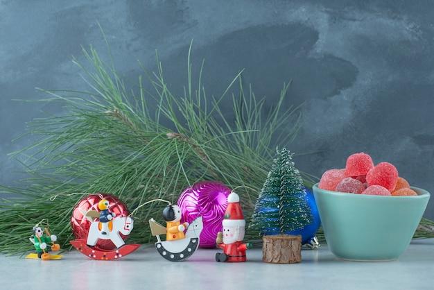 Een blauw bord van marmelade met klein feestelijk kerstspeelgoed op marmeren achtergrond. hoge kwaliteit foto Gratis Foto