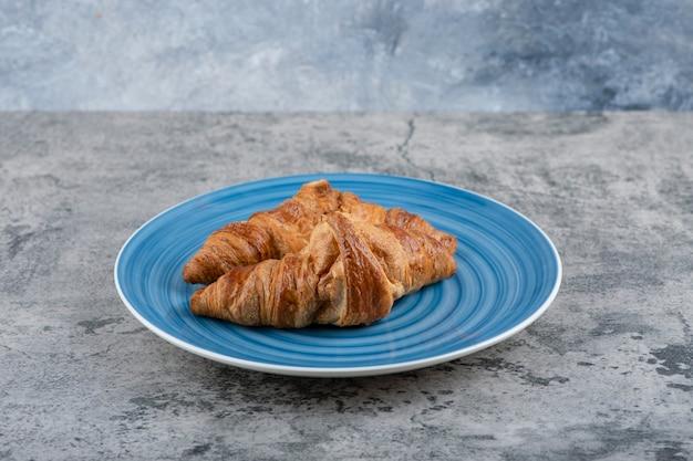 Een blauw bord van twee eenvoudige verse croissants op een stenen tafel. Gratis Foto