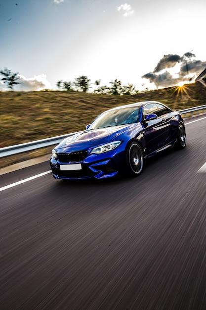 Een blauwe sedanauto die op de weg in het zonnige weer drijven. Gratis Foto