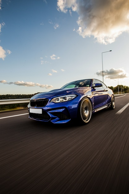 Een blauwe sport sedan testrit op de weg. Gratis Foto