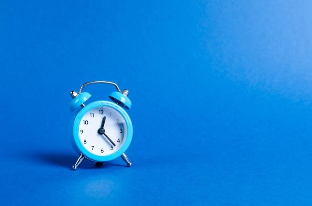 Een blauwe wekker op blauw Premium Foto