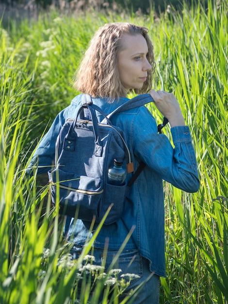 Een blik vanaf de achterkant van een blonde vrouw in een spijkerjurk trekt zijn rugzak uit op een pad in het hoge gras Premium Foto