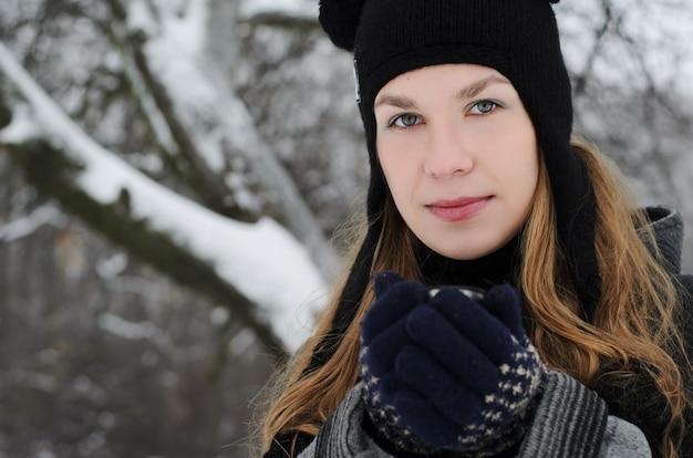 Een blond langharige meisje in een grappige hoed met panda oren drinkt koffie op een winterse dag buiten Premium Foto