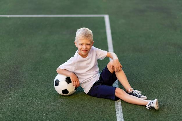 Een blonde jongen in een sportuniform zit met een voetbal op een voetbalveld Premium Foto
