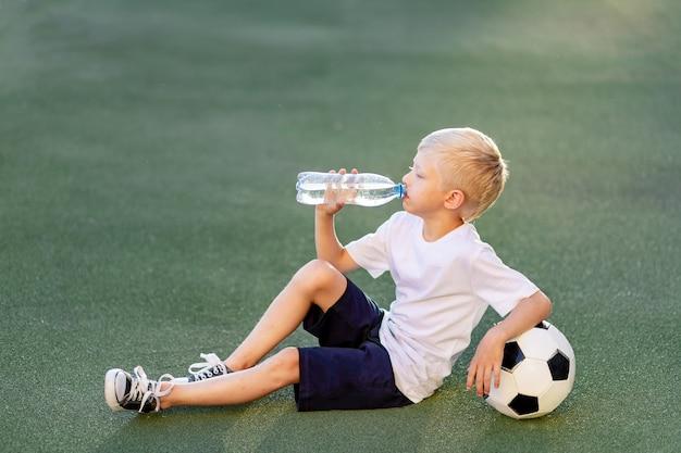 Een blonde jongen in een sportuniform zit op een voetbalveld met een voetbal en drinkt water uit een fles Premium Foto