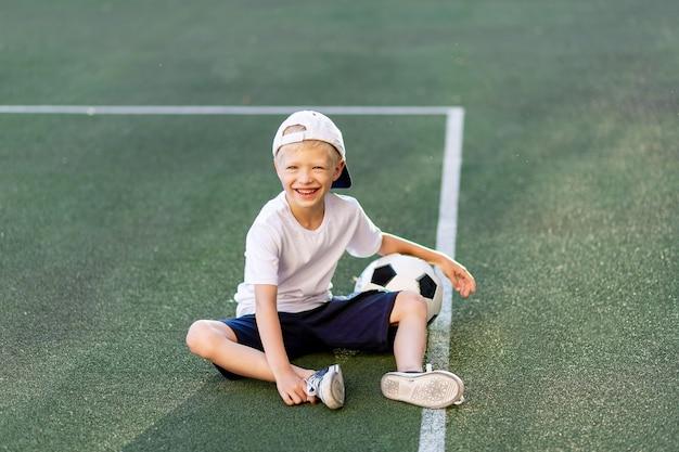 Een blonde jongen met een pet in een sportuniform zit op een voetbalveld met een voetbal Premium Foto