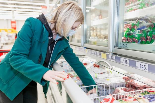 Een blonde vrouw met een medisch masker kiest producten op de vriesafdeling in een supermarkt. voorzorgsmaatregelen tijdens de pandemie van het coronavirus. Premium Foto