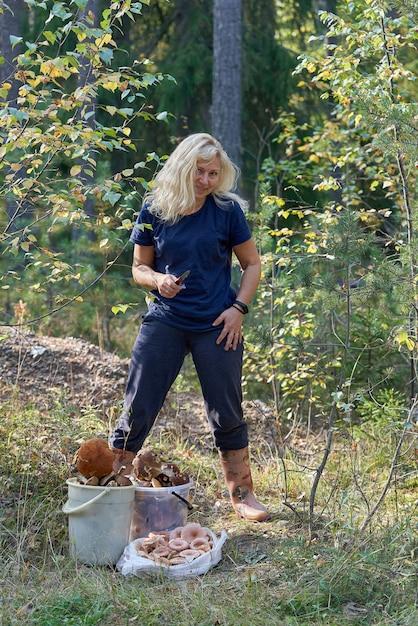 Een blonde vrouw met een mes in haar hand en haar losse haren staat in het bos naast de verzamelde paddenstoelen Premium Foto