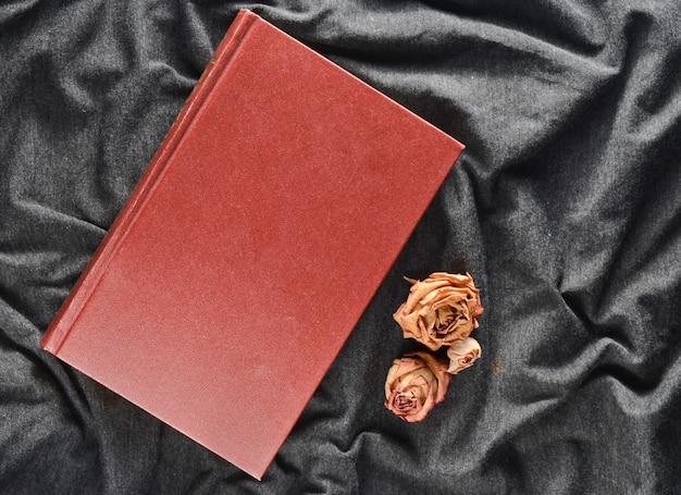 Een boek en gedroogde rozen op een grijze stof achtergrond. bovenaanzicht Premium Foto