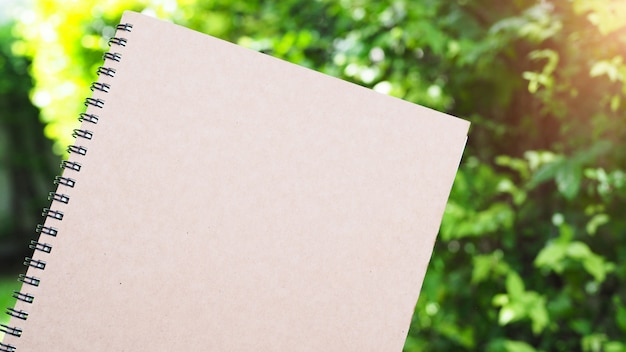 Een boek voor aantekeningen of om te werken heeft een bruine dekking in de tuin met een groene boom als achtergrond. Premium Foto