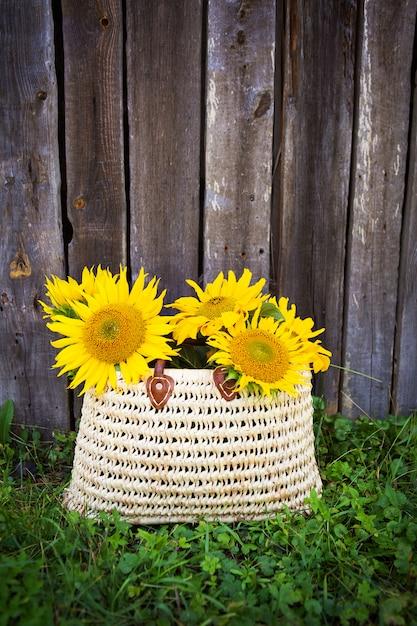 Een boeket grote zonnebloemen in een strozak staat bij een houten huis. Premium Foto