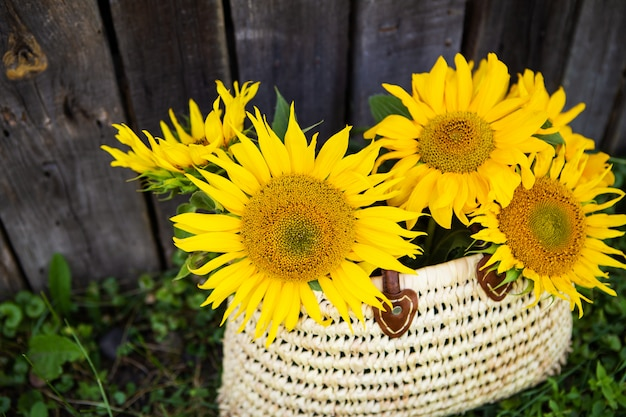 Een boeket grote zonnebloemen in een strozak staat bij een houten oud huis. Premium Foto