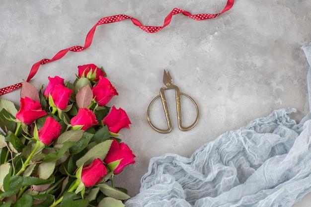 Een boeket rode rozen, oude schaar, een rood lint en gaas Premium Foto