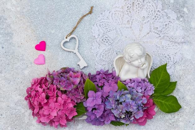 Een boeket van hortensia's, een engel gemaakt van keramiek, twee harten en een houten sleutel Premium Foto